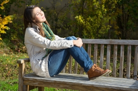 Young woman sitting on a park bench and enjoy the autumn.