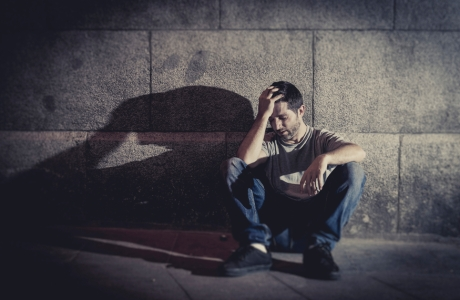 white wasted young man sitting on street ground with shadow on concrete wall feeling miserable and sad in urban scene representing depression and sickness